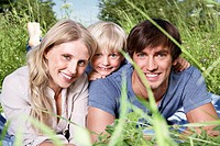 Germany, Cologne, Family lying in meadow, smiling, portrait