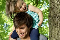 Germany, Cologne, Father carrying daughter on shoulders