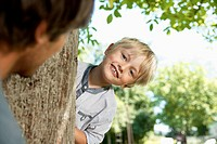 Germany, Cologne, Father and son playing head and seek, smiling