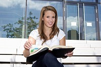 Europe, Germany, North Rhine Westphalia, Duesseldorf, Young student sitting on staircase with book, smiling, portrait