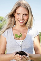 Germany, Cologne, Young woman holding seedling, smiling, portrait