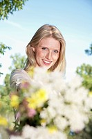 Germany, Cologne, Young woman holding wild flowers, smiling, portrait