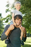 Germany, Cologne, Father carrying son on shoulders, smiling, portrait (thumbnail)