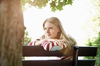 Germany, Cologne, Young woman sitting on park bench, smiling (thumbnail)