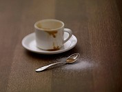 Coffee cup with saucer and spoon on table, close up