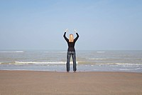 Belgium, Young woman meditating at North Sea