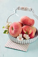 Peaches in basket with blossom on table
