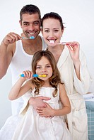 Parents and daughter cleaning their teeth in bathroom