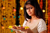 Portrait a woman holding pooja thali with dias