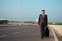 A businessman walking on the road pulling his trolly bag