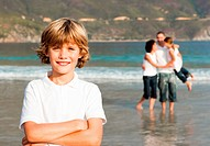 Cute boy on a beach with his parents and his sister in background