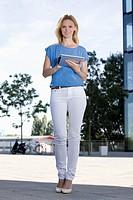 Europe, Germany, North Rhine Westphalia, Duesseldorf, Mid adult woman using digital tablet, smiling, portrait
