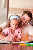 Radiant father helping her daughter for homework
