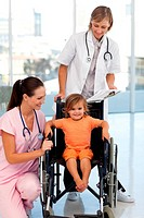 Doctors with a little girl sitting on a wheelchair