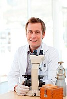 Male scientist looking through a microscope