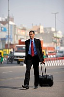 Businessman walking on the road pulling roller suitcase