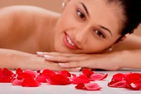 Young woman looking at rose petals