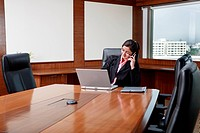 Businesswoman operating mobile phone, using laptop