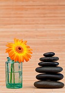 Orange snflower in a glass flask beside a black stones stack