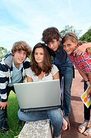 Teenagers sitting outside with laptop computer