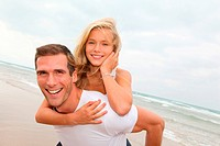 Man giving piggyback ride to blond girl by the sea