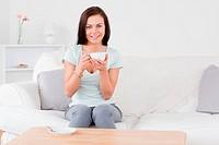 Smiling dark_haired woman drinking tea