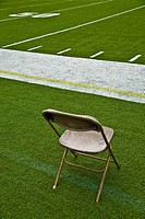 Folding chair on the sideline of an athletic field