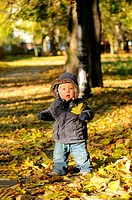 Toddler playing in the park in autumn