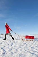 Woman pulling a sleigh with a suitcase