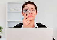 Office worker looking through a magnifying glass