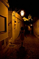 Girl in white walking down a street at night