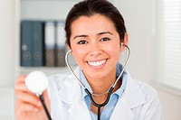 Beautiful female doctor using a stethoscope while looking at the