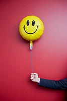 Business man holds a happy face balloon