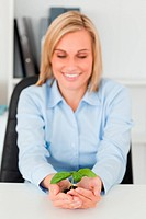 Smiling businesswoman looking at little green plant