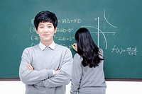 boy standing with his arms folded and girl solving a problem on the blackboard