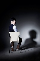 schoolboy sitting on the chair in a dark room