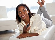 African American woman holding a TV remote control