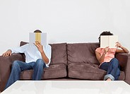 Young couple reading books apart on the couch