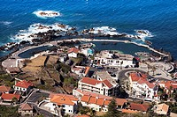 Overhead of town and natural swimming rock pools from Miradouro da Santinha, Madeira, Portugal
