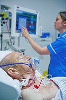 Intensive care patient. Nurse attending to a male patient in the intensive care unit of a hospital. He is attached to a respirator to help him to brea...