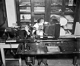 Micrography metallurgy analysis. Researcher in the 1930s using a new photomicrograph design right to analyse the structural effect of corrosion on met...