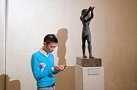 Paris, France, Young Asian Man Using Smart Phone Application on his Iphone in the Louvre Museum, Egyptian Antiquities Sculptues
