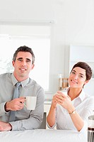 Smiling couple drinking coffee looking into the camera