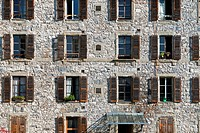 facade of stone wall residential building with plenty of windows with wooden shutters, old part of Geneva, Switzerland