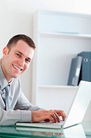 Happy businessman typing on his laptop