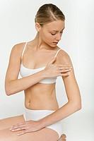 Young woman kneeling in underwear, applying moisturizer to shoulder
