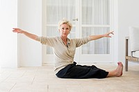 Mature woman practicing yoga on floor