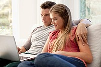 Couple using laptop on sofa (thumbnail)