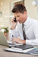 Businessman working with laptop and mobile phone (thumbnail)