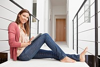 Woman sitting on balcony with digital tablet